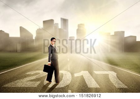 Young Asian businesswoman standing on the road while carrying a briefcase with numbers 2017
