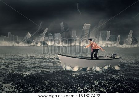 Young businessman standing on a boat while balancing his body shot at the sea with a sinking town
