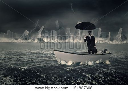 Businessman wearing a gas mask and standing in the boat while holding umbrella with a sinking town on the sea