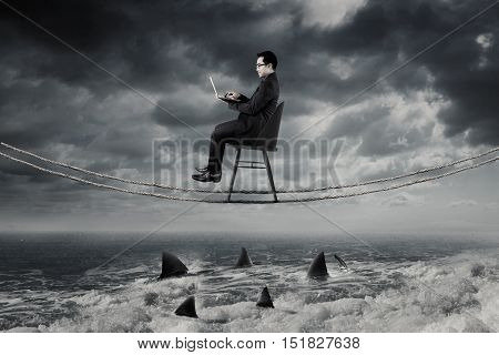 Young businessman working with laptop computer on the rope while sitting on the chair above dangerous sharks on the sea