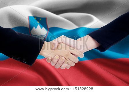 Image of a cooperation handshake with two people hands closing an agreement by shaking hands with flag of Slovenia