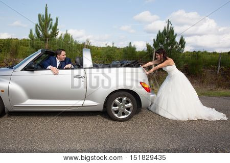 Handsome groom sitting in convertible car while bride pushing it