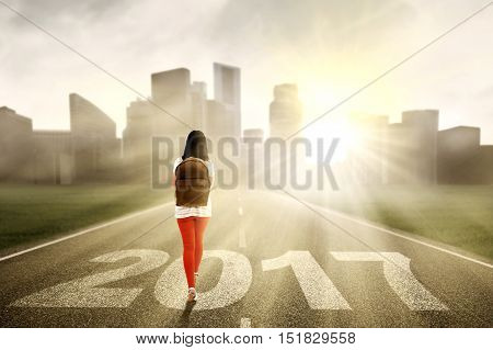 Image of a female student walking on the road while carrying backpack with numbers 2017