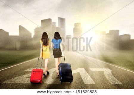 Two girls walking on the road while carrying suitcase with numbers 2017 and bright sunlight