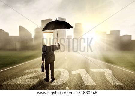 Image of a male worker with cardboard head standing on the road while holding umbrella with number 2017 and looking at a town