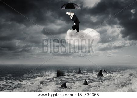 Businessman standing on the cloud while holding umbrella and looking down at dangerous sharks on the sea