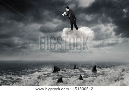 Young businessman standing on the cloud and shouting with a megaphone above dangerous sharks on the sea