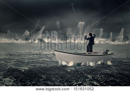 Image of a stressful businesswoman standing in the boat while looking at a sinking town on the sea