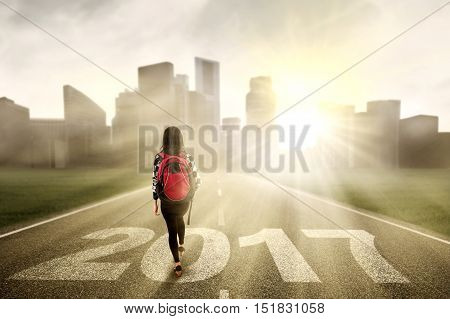 Back view of a female college student walking on the road with numbers 2017