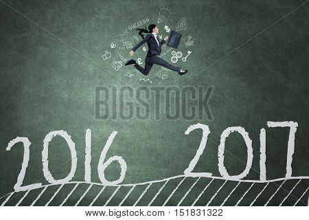 Female entrepreneur jumping on the blackboard through a gap and toward number 2017