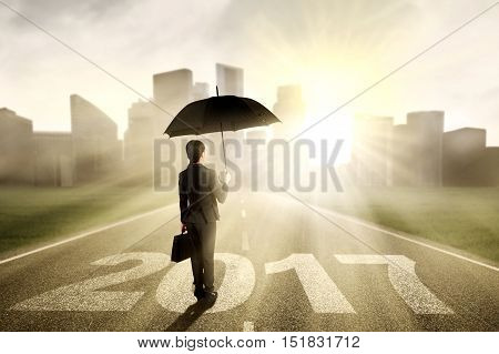 Young businesswoman standing on the street while holding umbrella with numbers 2017 and looking at a town