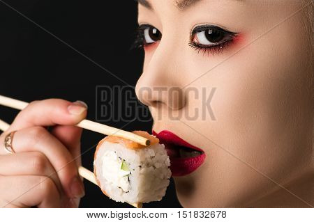 korean teenager girl eating roll closeup isolated on black background