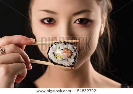 young Korean girl with roll closeup isolated on black background