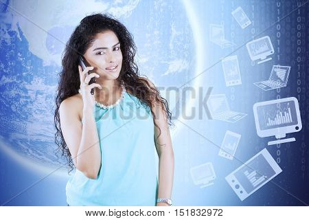 Young woman speaking on the mobile phone with earth background and financial graph on computer
