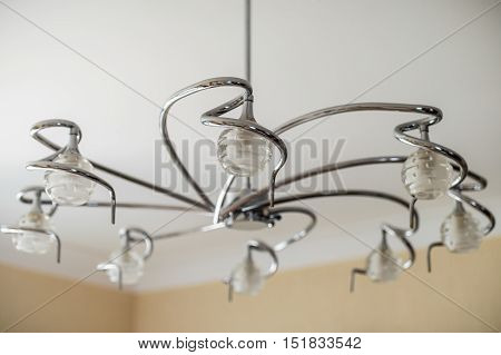 metal chandelier with glass shades hanging on the white ceiling