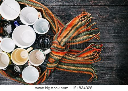 Variety of tea cups and mugs togethered with striped scarf. Flat lay