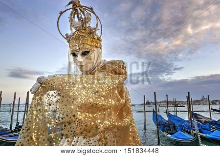 VENICE, ITALY - FEBRUARY 15, 2015: An unidentified people on golden costume in front of a gondolas pier during the Carnival of Venice