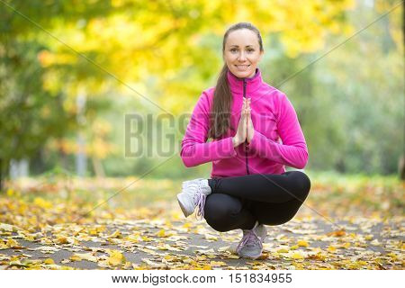 Beautiful young sport woman practicing yoga, sitting in squat, Half Lotus Toe Balance, variation of Utkatasana, working out outdoor on autumn day wearing bright sportswear, full length