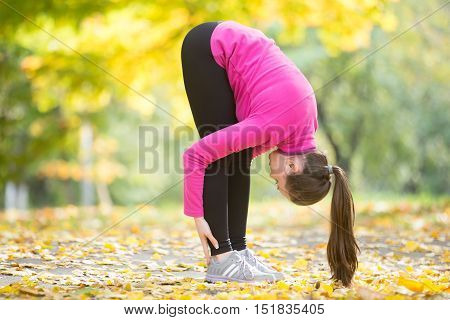 Sporty beautiful young woman practicing yoga, doing uttanasana intense stretch pose, Standing forward bend or head to knees pose , working out outdoors in autumn park. Full length, profile view