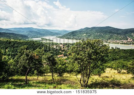 View from Ruin castle of Visegrad Hungary. Greenery and Danube river. Travel destination. Sightseeing cruises. Forests clouds and flowing water.