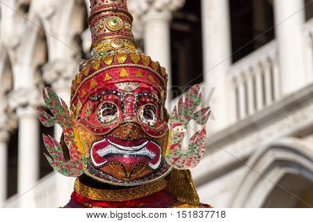 VENICE, ITALY - FEBRUARY 15, 2015: An unidentified person on a oriental style mask posing posing in front of the Doges Palace during the Carnival of Venice