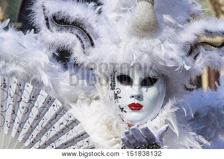 VENICE, ITALY - FEBRUARY 15, 2015: An unidentified woman in a beautiful white costume, holding a fan and sending kisses at the Carnival of Venice
