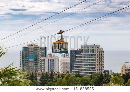 Cable car with a trailer over the picturesque arboretum in the resort town.