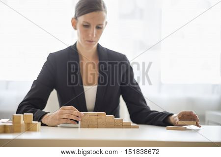 Businesswoman building a graph or ladder of success using small wooden building blocks stacked in an increasing profit and return stepped format.