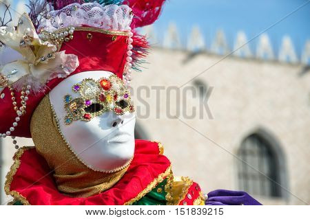 VENICE, ITALY - FEBRUARY 15, 2015: Portrait of an unidentified person on a colorful carnival costume, posing in front of the Doges Palace at Venice Carnival