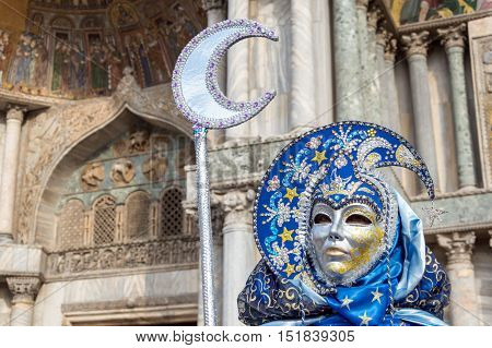 VENICE, ITALY - FEBRUARY 15, 2015: An unidentified person wearing a beautiful blue costume and holding a silver crescent at Venice Carnival