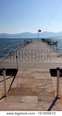 Wooden pier into the sea. At the end of the pier flag of Turkey. Mountains in the background.