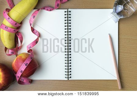 Healthy eating concept tape measure fruit and water bottle on a wooden background blank copy space notebook