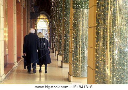 Bologna December 27 2015: elderly couple walks under the arcades of bologna decorated for Christmas festivities