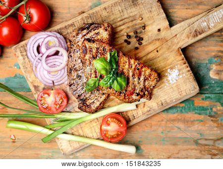 juicy steak, basil and tomatoes on old wooden background