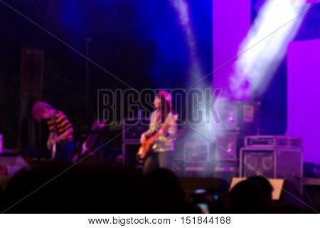 Blurred image of Guitarist of girl band perform on stage in music festival.