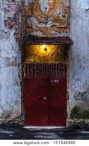 maroon door of an old house with peeling walls