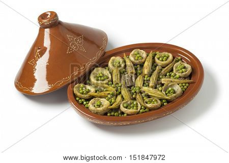 Moroccan oval tajine with meat, okra, green peas and artichoke hearts on white background