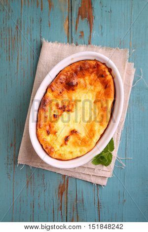 Cottage cheese casserole in white dish on a blue background