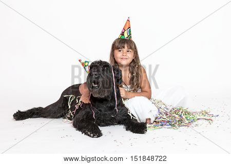 Cute smiling tanned little girl in white dress with paper hat on her head is embracing Giant Black Schnauzer dog on the white background looking to the right side.