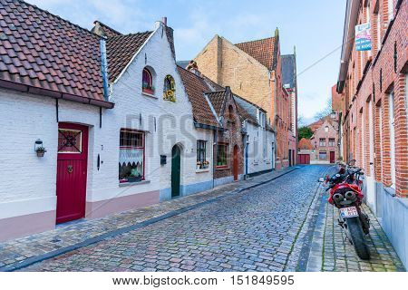 Brugge (Bruges) - February 2016, Belgium: A typical street of Brugge with traditional brick houses and modern motorcycle parked at the wall