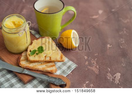 Homemade lemon curd on the toast on concrete background.