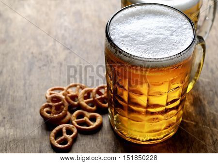 cold beer in a mug and chips on a wooden background