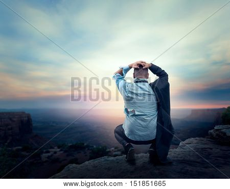 Businessman on the edge of the mountain