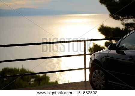 Car parked at edge of viewpoint in mountain over sea on summer evening