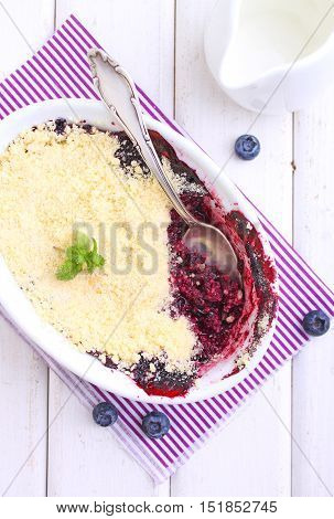 crumble with blueberry bilberry in white plate on a white background.