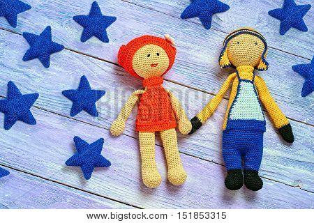Handmade Knitted Amigurumi Dolls Hold Each Other's Hands On The Wooden Background With Stars Surroun