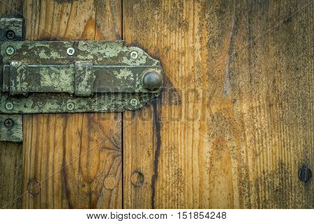 Metal latch from an aged wooden door - Wooden door from a german stable with its rusty metal latch and aged wooden planks. Good frame with copy space on the right side for your text.