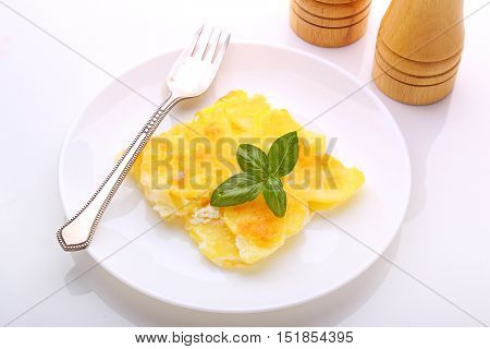 Potato gratin with cheese on a white plate