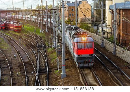 Electric locomotive pulling high-speed train on rails. Technical railway station - operational locomotive depot. Transport infrastructure of Russian Railways Saint-Petersburg