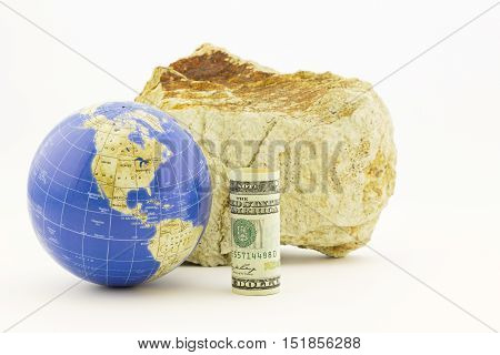 American currency with globe in front of firm rock reflects the global influences of economic policies. Horizontal still life with copy space.